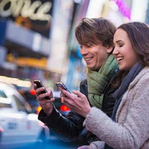 Young couple competing on cell phones, New York City, USA